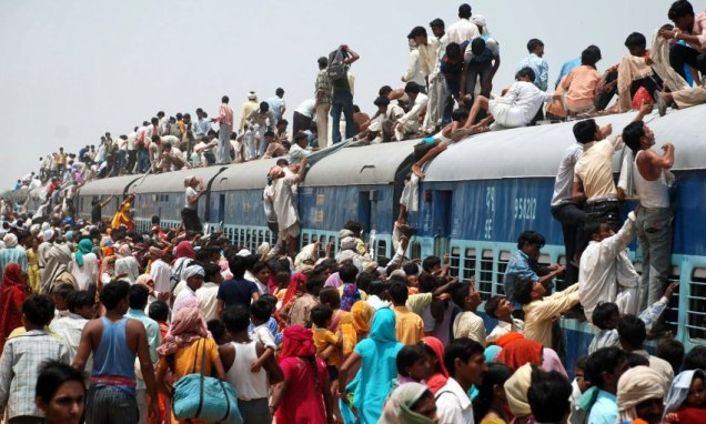 Hindu devotees try to board crowded passenger train in Mathura